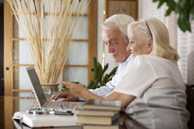 An older couple managing their finances together on a computer via Online Banking